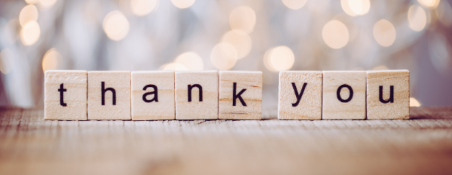 scrabble tiles spelling out thank you on glittery background