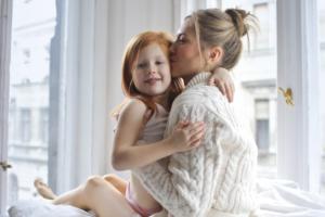 mom holding little girl on her lap, kissing her cheek